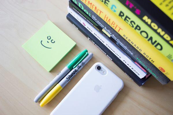 積み重ねられた本と電話とペンと付箋