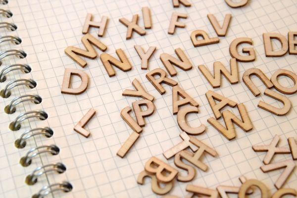 ノートの上に散らばったアルファベットのブロック