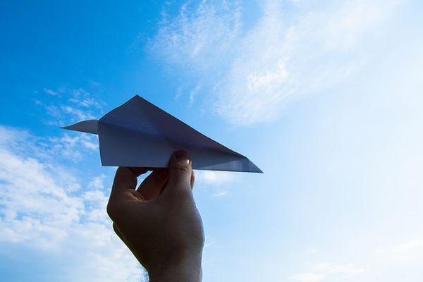 空に飛ばそうとしている紙飛行機