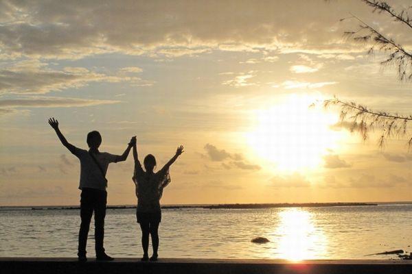 海に向かって手を上げるカップル