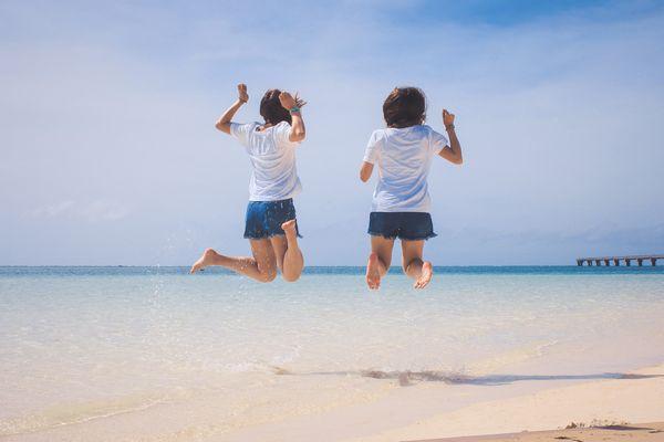 海に向かってジャンプする2人の女の子