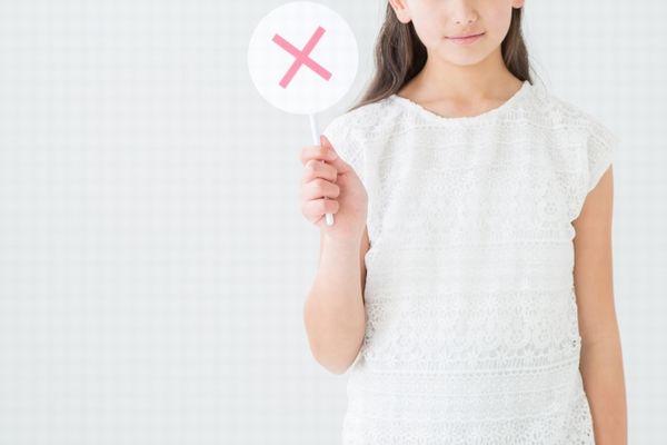 バツ印の札を上げる女の子