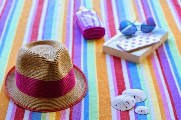 敷物の上に並べられた帽子と日焼け止めや本